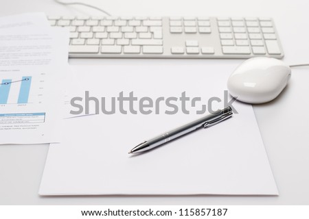 Silver pen and paper on office desk keyboard with mouse