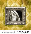 Silver picture frame hung against floral wallpaper background/ Yellow - stock photo
