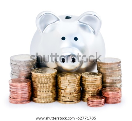 Silver piggy bank looking over top of stacked European coins, isolated on white background