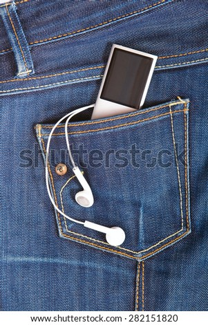 Silver player in jeans pocket with headphones - stock photo