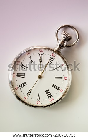Silver pocket watch shows the time on a white background