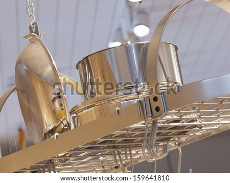 Silver pot rack with dishwares.