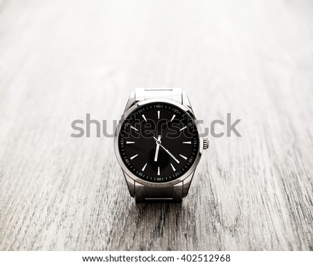 Silver reflective wrist watch, clock with black dial and silver pointers resting on wood surface. Selective focus on the clock. - stock photo