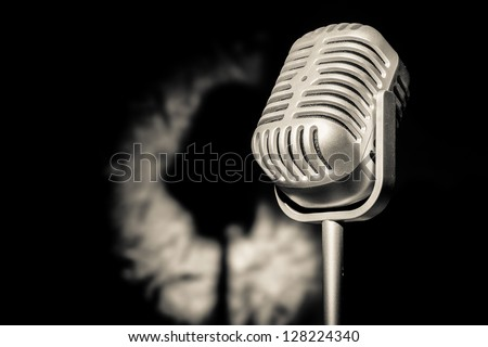 Silver retro microphone in spot light with shadow backdrop - stock photo