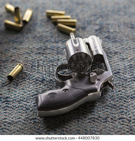 Silver revolver gun with bullets, gradient blur - stock photo