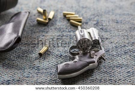 Silver revolver gun with bullets, gradient blur - stock photo