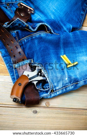 silver revolver in the pocket of blue jeans - stock photo