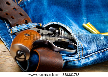 silver revolver nagant in the pocket of old blue jeans. close up - stock photo