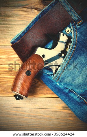 silver revolver nagant with brown handle  in the pocket of old blue jeans. close up. instagram image filter retro style - stock photo