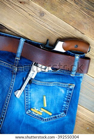 silver revolver nagant with brown handle in the pocket of old blue jeans. copy-space. close up - stock photo