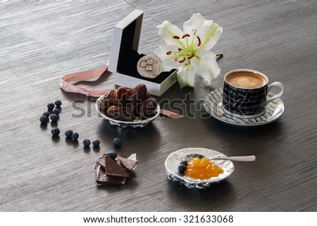 Silver ring gift setting with morning coffee, dry dates, orange marmelade, blueberries and white lily - stock photo