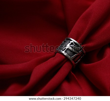 Silver ring lying on red  fabric. - stock photo