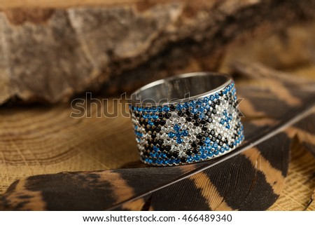 Silver ring with blue and black gemstones on wooden background. Shallow focus