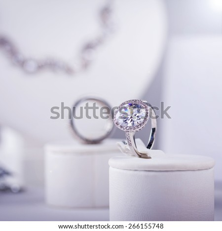 Silver ring with little diamonds. Isolated on grey. Lens flare. Small depth of field - stock photo
