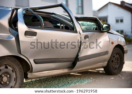 Silver sedan car written off in a traffic accident standing in the road surrounded by shattered glass from its destroyed windscreen and windows, with a flattened roof and crumpled coachwork - stock photo
