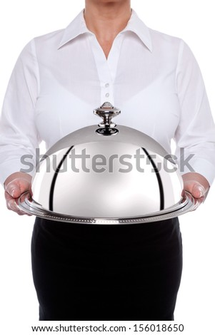 Silver service waitress holding a shiny metal dome or cloche as it's also known, isolated on a white background. - stock photo