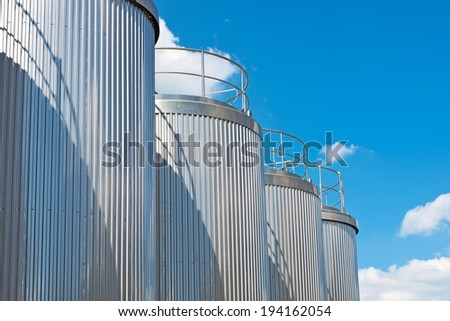 Silver silos and tank - industrial infrastructure in wide lens - stock photo