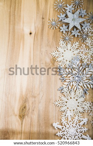 Silver snowflakes on a wooden table. Christmas decorations closeup.