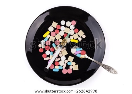 Silver spoon full with  medicine a syringe and colored pills in the background - stock photo