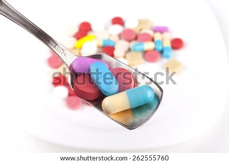 Silver spoon full with  medicine and colored pills in the background - stock photo