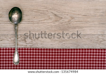 Silver spoon on checkered table cloth and old wooden board - stock photo