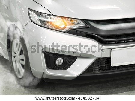 Silver Sport Car with detail on spinning and smoking wheels/tires doing burnouts, dynamic photo - stock photo