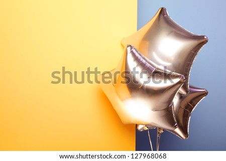 Silver star shaped balloons on yellow and blue background - stock photo