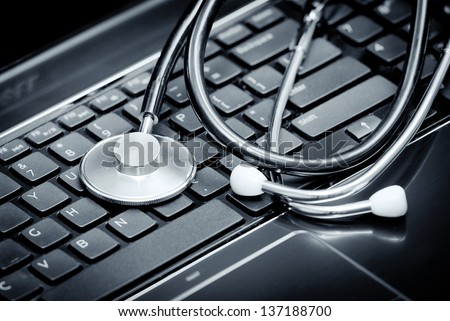 Silver stethoscope lying down on an laptop - stock photo
