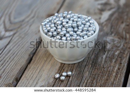 Silver sugar sprinkles in a bowl. Natural light. Selective focus.  - stock photo