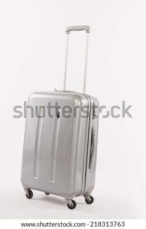 Silver suitcase with long handle against white background