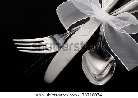 Silver table cutlery or flatware comprising of spoon, knife and fork isolated on a black background - stock photo