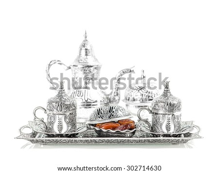 Silver tableware and dates. Oriental hospitality concept with tea or coffee cups - stock photo