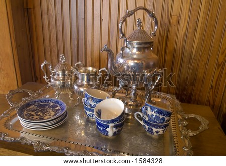 silver tea service with china, teapot and platter on buffet table