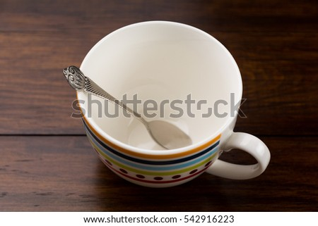 Silver tea spoon in white ceramic fancy coffee cup on wooden background.
