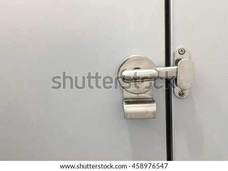 Silver toilet door rolling lock on the gray  wall