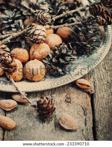 Silver Tray with Natural Pine cones, Walnuts, Almonds, Nuts on Wooden Background, holiday decoration, toned effect - stock photo