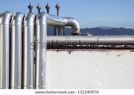 Silver tubes from an industrial installation over a roof - stock photo
