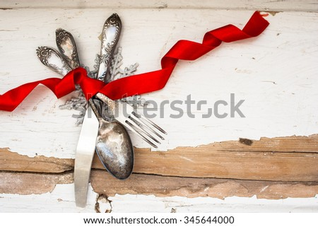Silver utensils on shabby wooden background tied with ribbon and snowflake on the background - stock photo