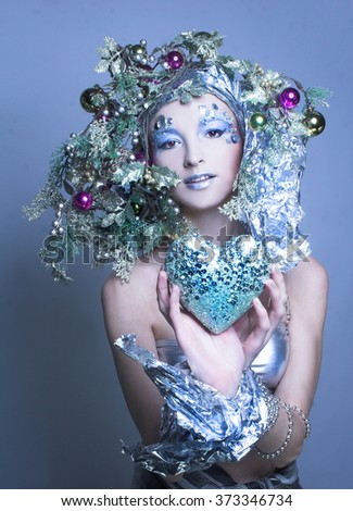 Silver Valentine. Young woman in creative image posing with heart