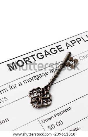 Silver vintage key against mortgage agreement - stock photo