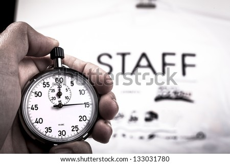 Silver vintage metallic chronometer in a hand with a white staff shirt in the background - stock photo