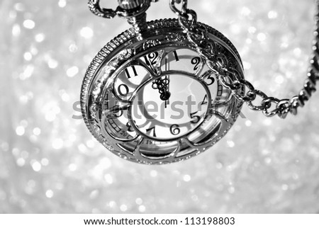 Silver vintage pocket watch with chain as viewed from above over bokeh background.  Side lighting with shadows for effect. Black and white macro with shallow dof.  Selective focus on the number 12.