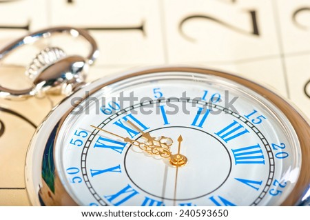silver watch with gold hands and a calendar closeup - stock photo