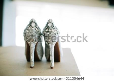 Silver Wedding High Heels on Table Illuminated - stock photo