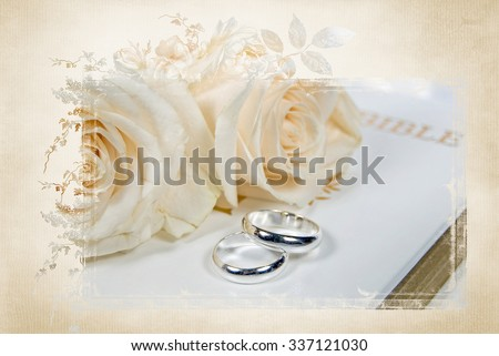 silver wedding rings and white rose bouquet on Holy Bible with elegant mask frame - stock photo