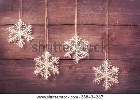 Silver white christmas snowflakes over vintage wooden background. Xmas card. Toned image