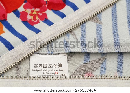 "Silver zipper and white washing tag label with the inscription "" Designed with passion &  love in Germany "" on a background of striped white blue jersey fabric with red flowers - stock photo"