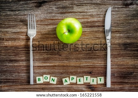 Silverware and apple on wooden vintage table with Bon apetit sign - stock photo