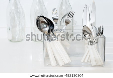 Silverware in a box on top of a kitchen counter