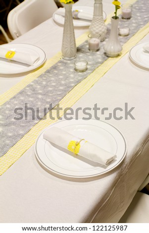 Silverware is wrapped up in a napkin for a wedding dinner reception in an old barn. The wedding decor includes a japanese or chinese influence with colors of white, grey (or gray) and yellow.